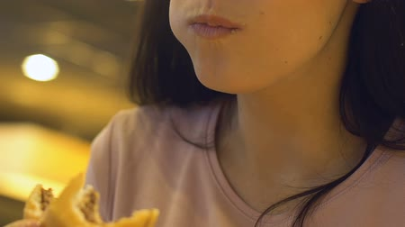 жевать : Young hungry woman with appetite eating tasty burger at fast food restaurant