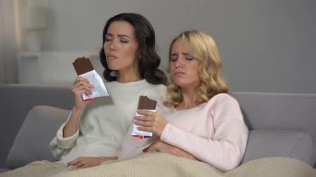 obżarstwo : Female friends sitting on sofa and enjoying sweet chocolate taste, hormones Wideo