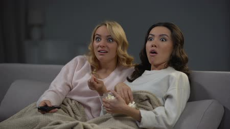 watch tv : Two shocked women eating popcorn and watching interesting TV program, rest