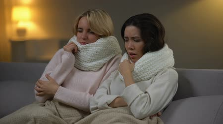 kaszel : Two sick girls sitting with scarfs in bed and sneezing, flu virus, health care