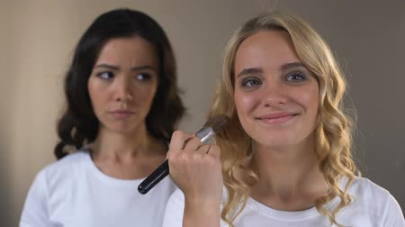 jealous : Woman jealously looking at her beautiful friend applying face powder, complex Stock Footage