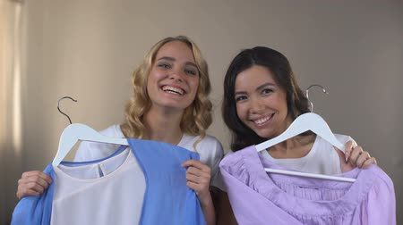 решить : Two smiling female friends choosing clothes in shopping moll, fit room, outfit