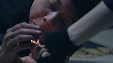ghetto streets : Teenage beggar lighting cigarette to friend, addiction among homeless children