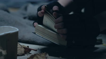 holy book : Trembling beggar opening Bible, searching salvation, faith in god, enlightenment Stock Footage