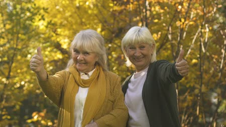 allowance : Happy old women showing thumbs up, enjoying benefits for pensioners, slow mo