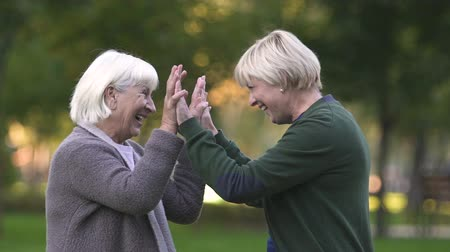 stáří : Old mother and adult daughter giving high-five, celebrating life, family love