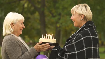 uzun ömürlü : Adult daughter wishes old mother happy birthday, giving cake, family celebration