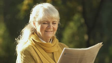 latest : Old woman reading good news in newspaper about pension reform, resting in park