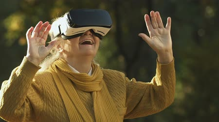 amadurecer : Old woman using VR headset, exploring virtual world, modern entertainment Stock Footage