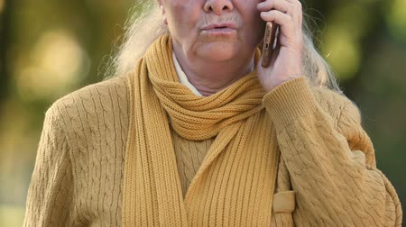 telefoniste : Old woman upset by bad news from phone, dissatisfied with mobile connection