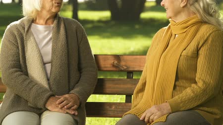 neighbor : Old women sitting on bench, discussing latest news, gossiping about neighbors