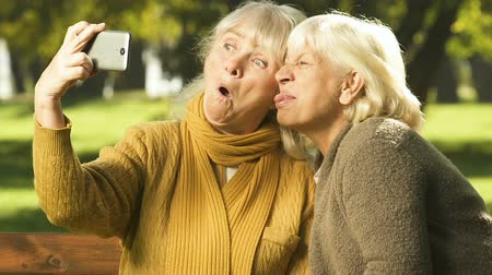 yüz buruşturma : Happy old women showing grimaces on cell phone, selfie app, happy time together