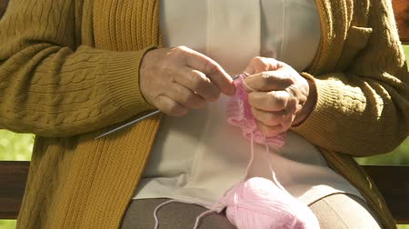 пенсионер : Granny knitting pink clothes for granddaughter, happy waiting for replenishment Стоковые видеозаписи