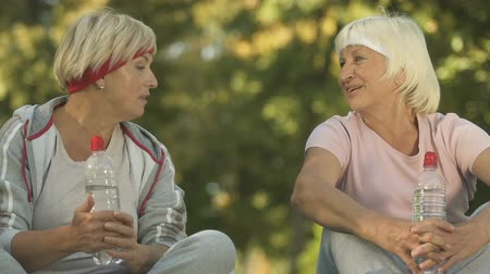 шестидесятые годы : Two female friends in sportswear talking after workout outside, sitting in park