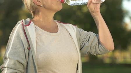 aerobica : Happy senior woman drinking water and smiling in camera, relax after training