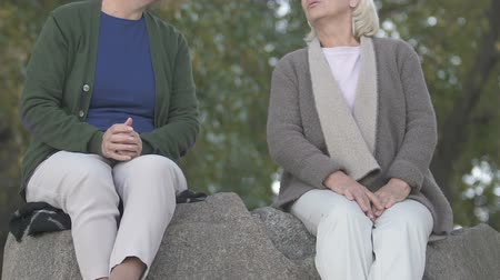 companionship : Two female pensioners talking, sitting together on river stone, friendship