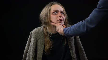forced : Man hand taking crying female face with bruises domestic violence sexual slavery.