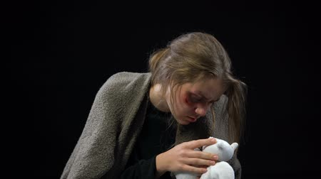 forced : Domestic violence victim hugging stuffed animal toy, finding consolation.