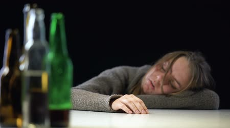 mistreatment : Addicted female sleeping on table after drinking alcohol, harmful health effect Stock Footage