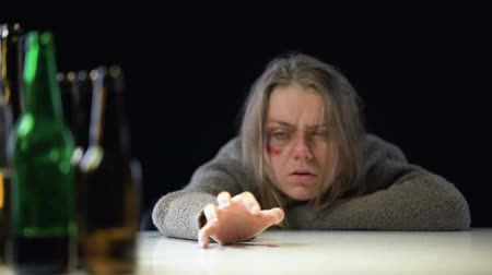 intimidated : Addicted weak-willed woman lying on table and trying to take bottle of beer