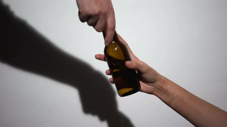 miserável : Hand giving self-inflicted alcohol addicted woman bottle of beer, mental disease Stock Footage