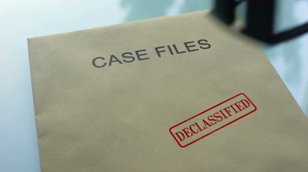 belgeleme : Case files declassified, hand stamping seal on folder with important documents Stok Video