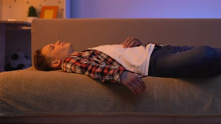 amado : Teen boy lying on sofa and dreaming about beloved girl, love at awkward age Stock Footage