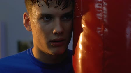 punching bag : Tired teenage boxer looking camera standing near punching bag, sport will power