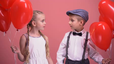 em forma de : Boy and girl holding red heart balloons and looking at each other, first love
