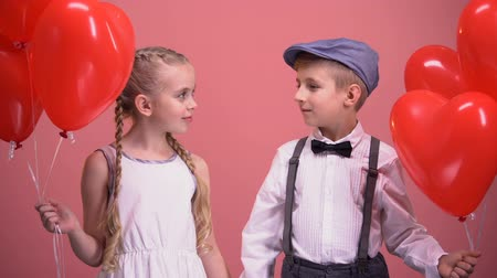 walentynki : Couple of little kids in love, holding red heart balloons, smiling into camera