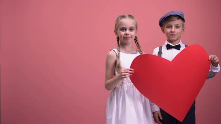 donate : Kids couple holding red heart cutout and smiling, valentines day, love concept