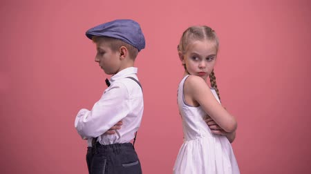 culpado : Sad kids couple standing back in silence after quarrel, isolated pink background