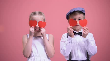 closing : Little boy and girl closing eyes with paper hearts, having fun on Valentines day
