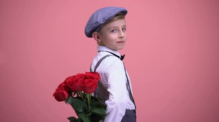 schoolkid : Little gentleman kid hiding roses behind back and turning to camera, smiling