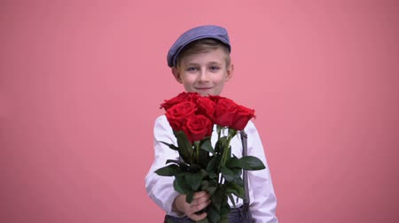 zdziwienie : Cute gentleman boy presenting bouquet of red roses into camera, Valentines day