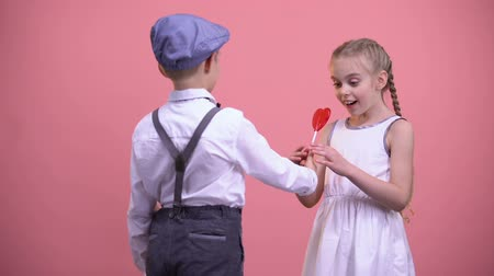 félénk : Little boy giving red heart-shaped lollipop to girlfriend, sweet romantic gift
