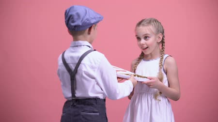 félénk : Little boy presenting chocolate candies to surprised girlfriend, Valentines day