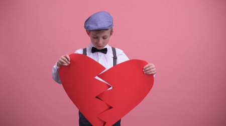 разорвал : Little boy in vintage clothes trying to fix red broken toy heart unrequited love