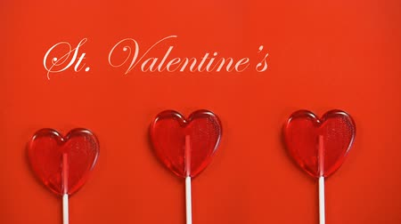 lolly : St Valentines Day text and heart-shaped lollipops appearing on red background