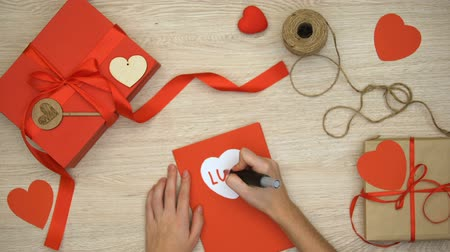 gratulací : Hand writing love word on greeting card lying on table with craft gift boxes