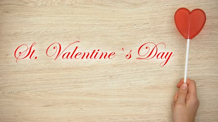 frase : St Valentines Day phrase on wooden background hand holding heart-shaped lollipop