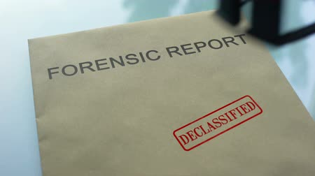 police sign : Forensic report declassified, stamping seal on folder with important documents Stock Footage