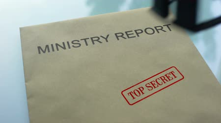 承認された : Ministry report top secret, stamping seal on folder with important documents