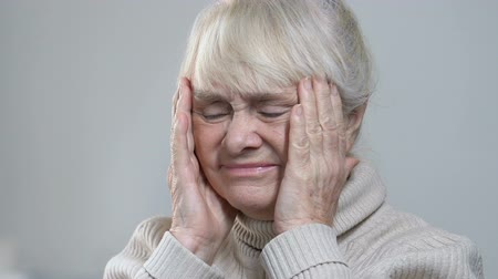helplessness : Wrinkled senior female suffering strong headache, massaging temples, healthcare