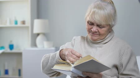 supportive : Supportive nurse giving elderly woman patient eyeglasses, aged lady reading book Stock Footage