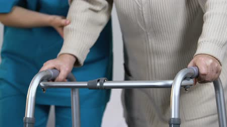 rebuliço : Nurse helping aging lady suffering arthritis to stand up and take walking frame Stock Footage