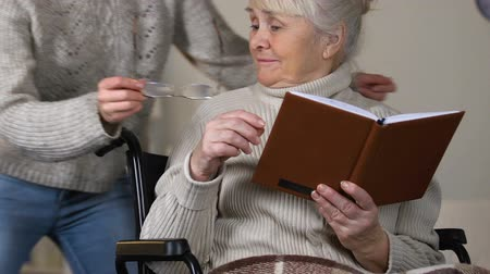 caregiver : Caring young lady giving eyeglasses to aged granny reading book in wheelchair