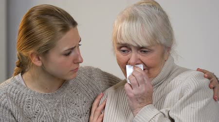 relações : Young lady comforting unhappy crying granny suffering loss, support in family