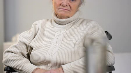 homesick : Upset elderly female looking at pills and glass of water, medication dependence Stock Footage