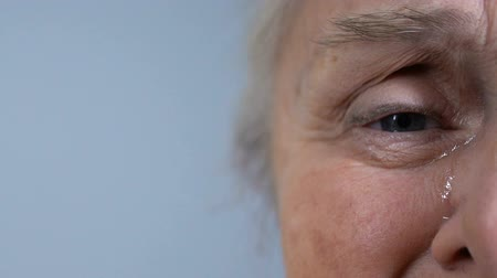 pŁacz : Unhappy crying wrinkled senior female looking at camera, half-face closeup